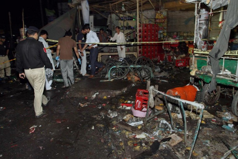 Pakistani police and security officers examine the site of an explosion in Multan, Pakistan, Sunday, Sept. 13, 2015. A police official said the blast outside of a bus terminal in central Pakistan killed several people and wounded tens. (AP Photo/Asim Tanveer)